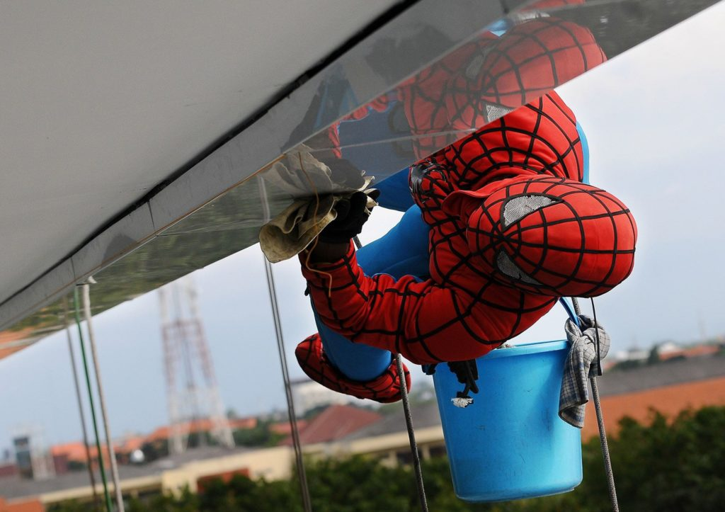 Image of someone dressed as Spiderman cleaning the windows